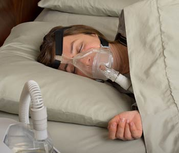 Senior woman using cpap machine to stop choking and snoring from obstructive sleep apnea